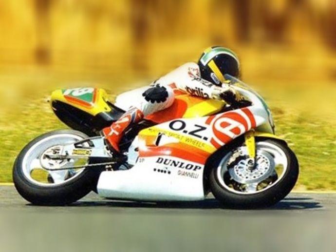 1990. Das OZ Aprilia Team ist da: ein innovatives Rennteam, dass in den 1990er Jahren mit der alles verändernden Aprilia, gefahren von Marcellino Lucchi, am World Moto 250GP teilnimmt.